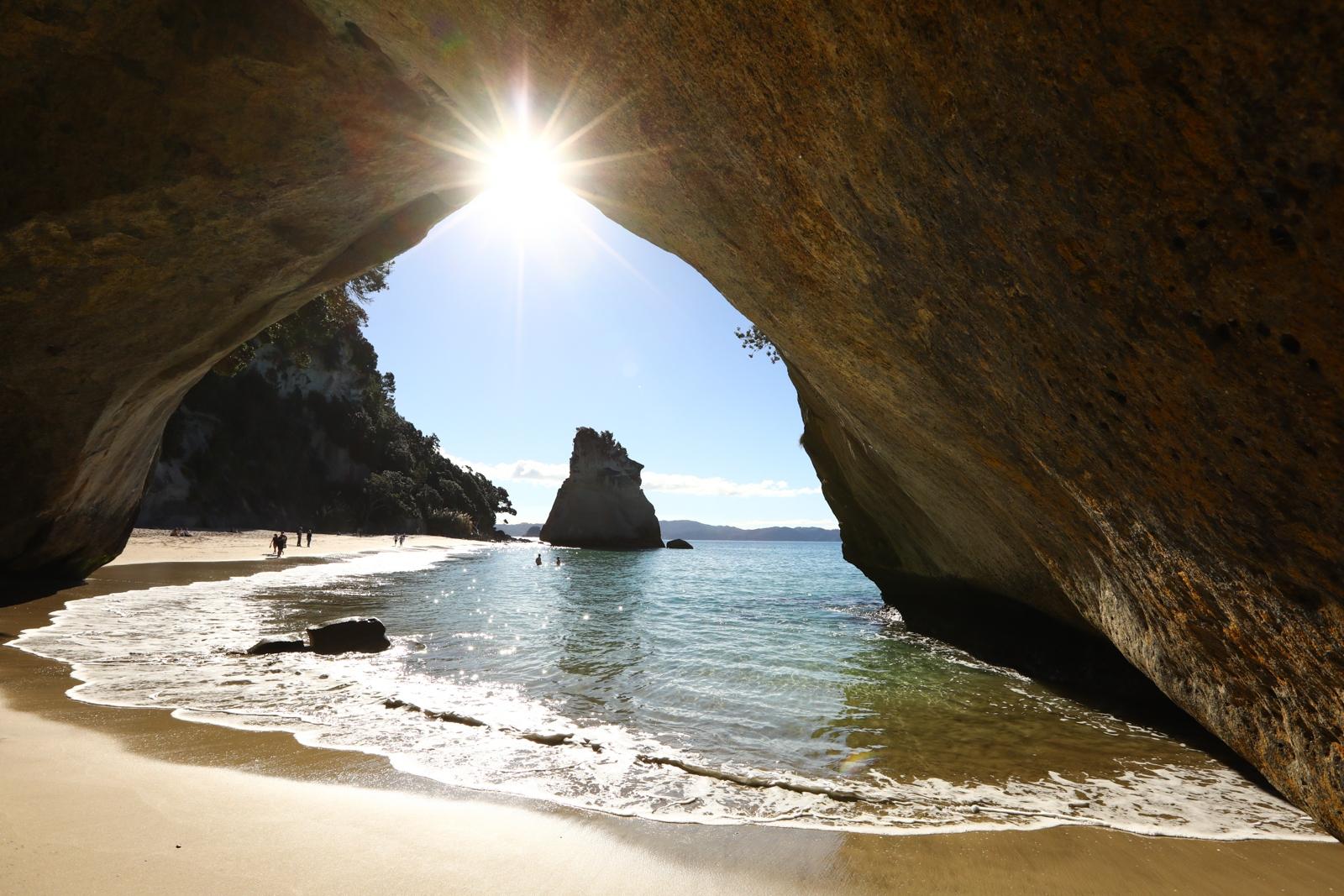 Raio de sol quando chegou ao ponto exato para a foto na Cathedral Cove, Nova Zelândia