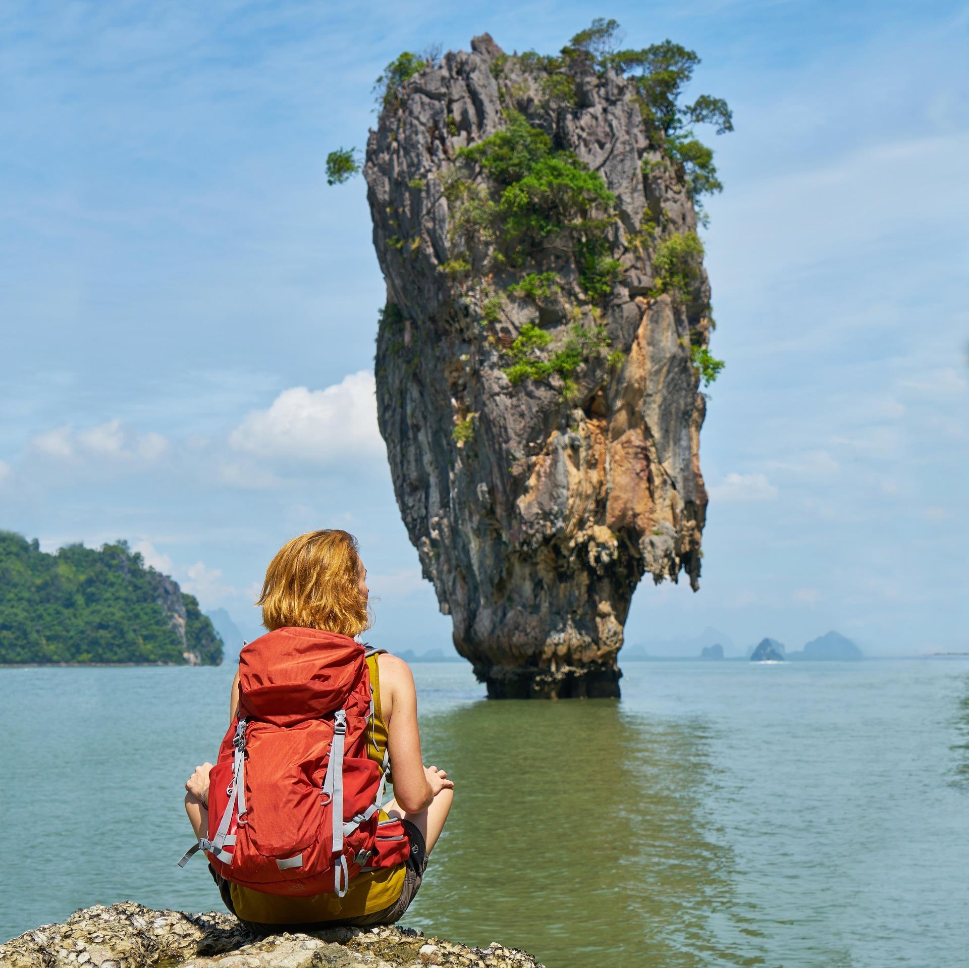 uma mulher com mochila sentada numa praia da Tailândia